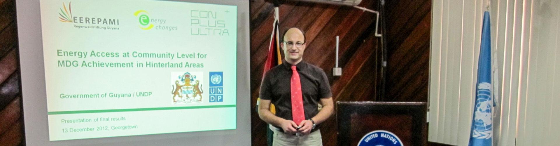 Foto: ein weißer Mann u.a. mit rotem Schlips steht vor einer Beamer-Leinwand mit Bild