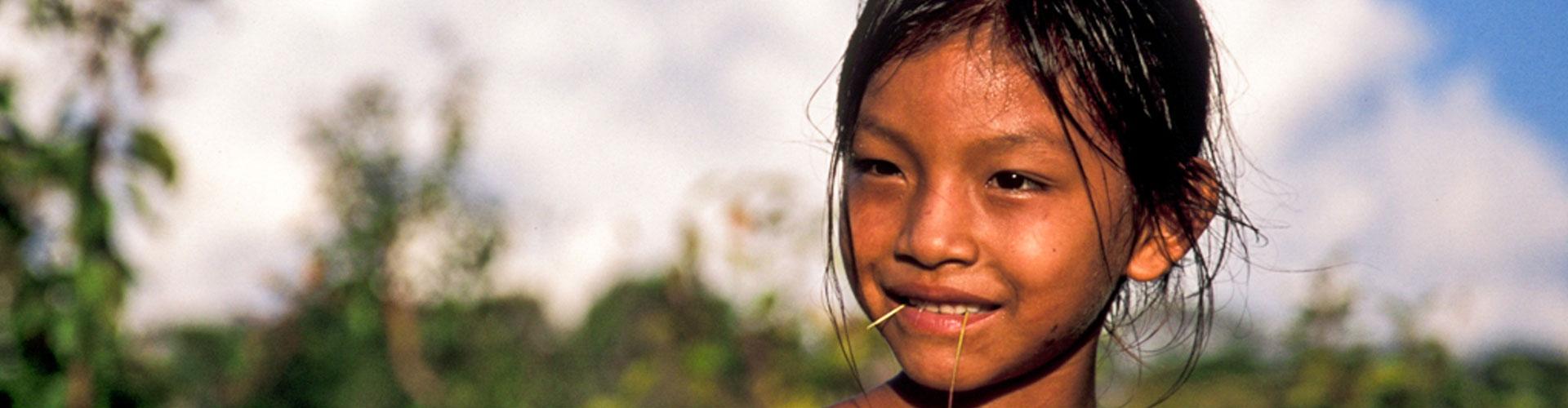 Foto: Kopf eines brasiliansichen Mädchens mit Strohhalm im Mund