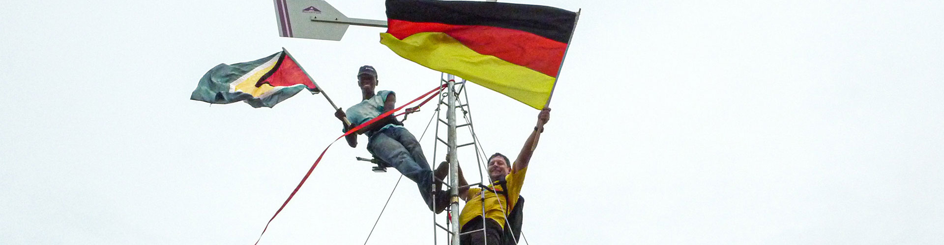 Foto: weißer Mann mit deutscher Nationalflagge und schwarze Frau mit guyanischer Nationalflagge auf einem Mast