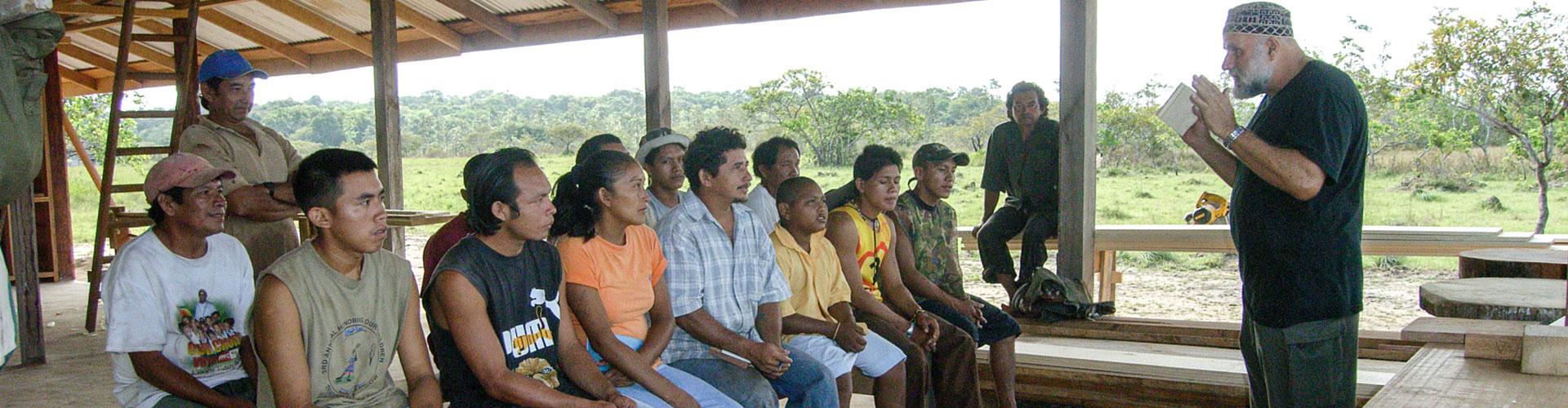 Foto: Mann mit angewinkelten Armen in Lehrerpose vor einer sitzenden Gruppe guyanischer Zuhörer