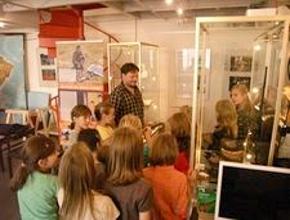 Foto: ein Mann spricht zu einer Gruppe Kinder zwischen Ausstellungsvitrinen