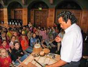 Foto: ein Mann hält einen Vortrag vor einer Gruppe Kinder