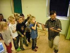 Foto: Mann hält Blasrohr für Kind, dass hinein bläst. Andere Kinder dahinter stehen an