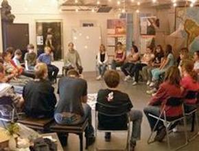 Foto: Jugendliche und Kinder sitzen in ein Kreis auf Stühlen