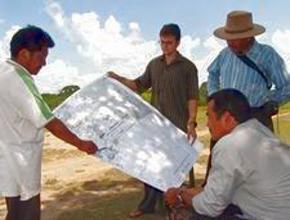 Foto: drei Männer beraten über einem ausgebreiteten Plan