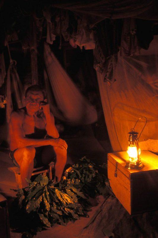 Foto: alter Mann sitzt neben einer Kiste mit leuchtender Laterne darauf