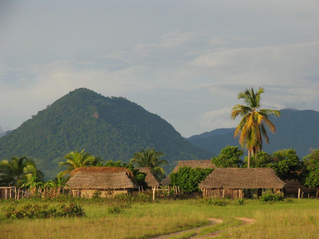 Foto: Landschaft, Dorf aus Bambushütten mit Bergen im Hintergrund
