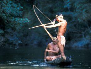 Foto: zwei Männer in einem Einbaum bei Jagen mit Pfeil und Bogen