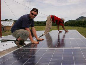 Foto: zwei Männer knien über mehreren aneinandergereihten Solarpanels und arbeiten daran