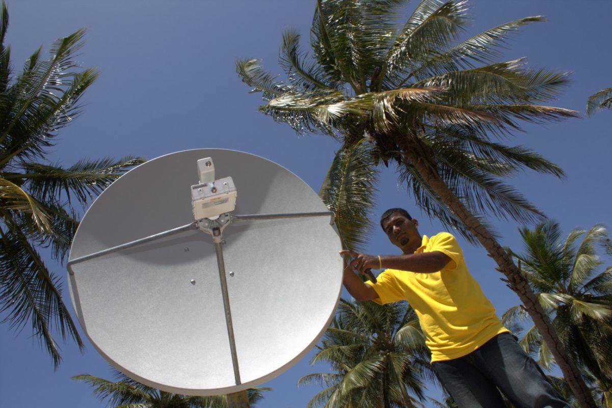 Foto: Mann steht neben einer Solarschüssel und hält ich an dieser fest