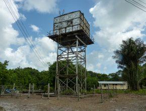 Foto: großer Stahlturm mit Behälter oben drauf neben freihängenden Stromleitungen