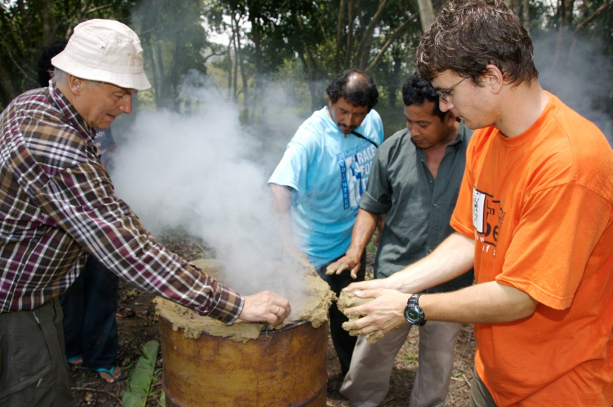 Foto: 4 Männer stehen um eine alte rauchende Öltonne und verschließen sie mit Lehm