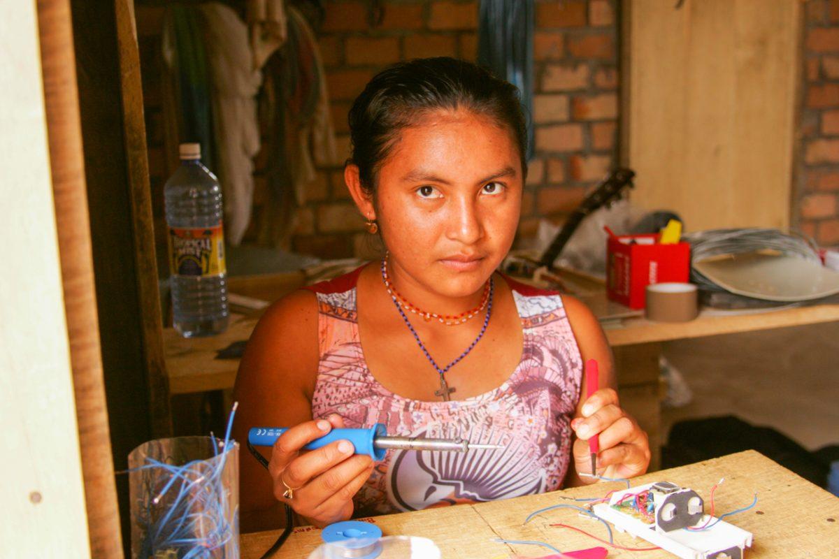 Foto: Frau sitzt an einem Tisch mit Lötkolben und bastelt an einem Gerät