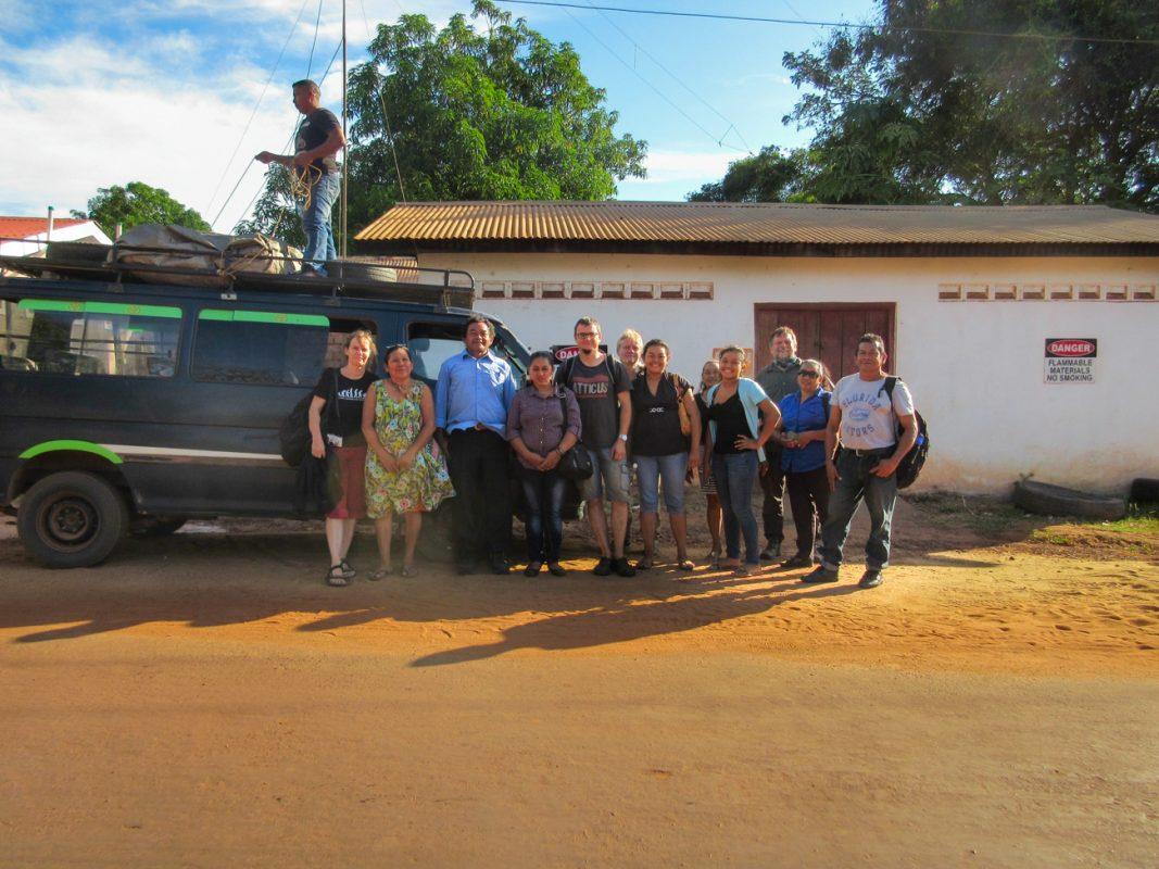Foto: Gruppe von Männern und Frauen stehen vor blauem Kleinbus mit Blick zum Betrachter.