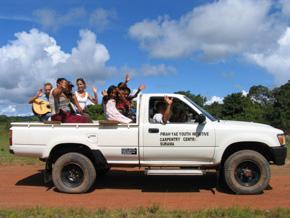 Foto: weißer Pickup mit winkenden Menschen auf der Ladefläche